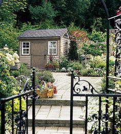 A cottage-style garden shed features several windows that light the interior of this small structure. The shed is cleverly positioned in the landscape, with a paving stone walkway that leads right to the door.