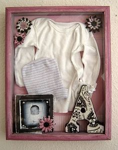 Shadow box holds first outfit, hospital cap, and newborn photo for remembering the first day of life.