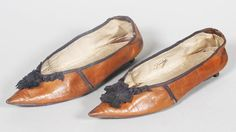 A pair of 18th century English lady's dress shoes, of buff leather trimmed with a chocolate brown silk rosette and edging.