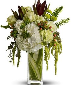 """""""Elegant Nature's Harmony"""" Arrangement: Arrangement Details:   An exotic mix of flowers including white hydrangea, leucadendron, red hypericum, green roses, green carnations and hanging amaranthus accented with bupleurum, sword fern and eucalyptus. Delivered in a clear, leaf-lined bunch vase."""
