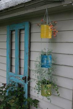 the doors, paint cans, hanging flowers, coffee cans, flower pots, tin cans, old doors, hanging planters, garden