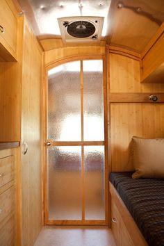 Pocket door / plexiglass .... still lets light through.  I'd put it between the kitchen/bathroom and the living area.