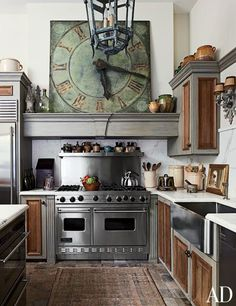 A kitchen inspired by Old World estates features an antique French clock and Viking range.