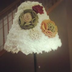 Covered an old lamp shade with felt flowers and ruffled trim