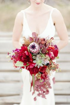 Red Charm peonies, red foliage, succulents, and proteas