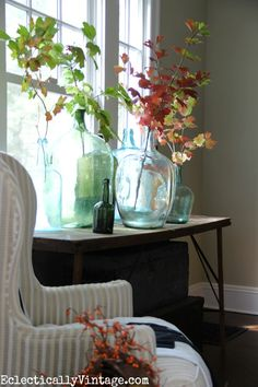 Vintage demijohns filled with colorful fall leaves - this fall home tour is gorgeous! eclecticallyvintage.com