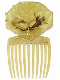 This Lalique hazelnut comb was made to be worn in December. The carved horn panel boasted hazel leaves, which covered two chestnuts. He textured the leaves and stem in gold, c. 1900.