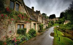 stone cottages with green doors & pink roses; Bibury, England