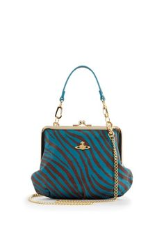 New for Autumn/Winter 2013-14 Vivienne Westwood has beautifully crafted the Tiger Collection. This playful evening bag comes stunningly produced in luxurious soft Bordeaux and turquoise faux leather. Exquisitely distinguished with a golden clasp closing, this dainty bag comes finished with a Westwood Orb on the front. The interchangeable 21cm short faux leather handle and 110cm golden shoulder chain make this a very versatile bag.