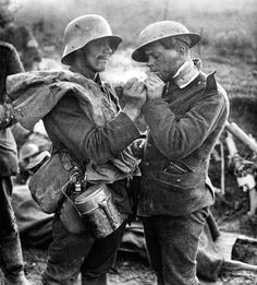 German and British soldiers share cigarettes during the 1914 Christmas Truce.