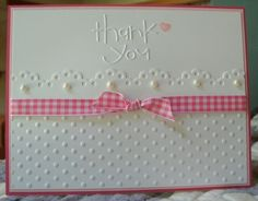 "White on white is impressive and even more so with little pops of pink.  Swiss dot embossing topped by a scalloped frame are perfect with the pearl accents.  Add and embossed ""thank you"" sentiment and pink/white gingham bow for a cute handmade card."