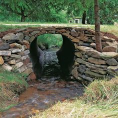 Learn how to build a stone culvert with dry-stacked and flared wing walls to divert water.