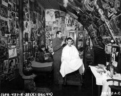 A multitude of pin-up pictures adorning the wall of the 533rd Bomb Squadron barber shop catches the eye of the customer as the barber gives him a trim. 381st Bomb Group, England, 1 December 1944.