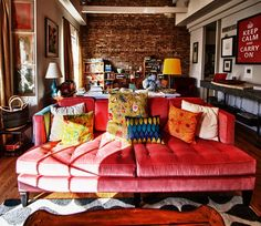 love this living room--a muted red couch plus colorful pillows, all against exposed brick wall.