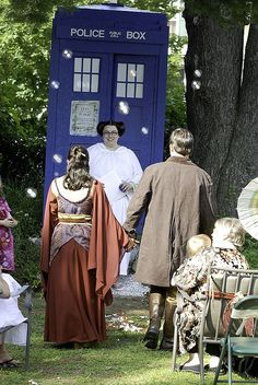 nerdvana wedding. bride and groom dressed as Inara and Mal, with Princess Liea officiating and the tardis in the background, and it looks like kaylee's umbrella off to the side