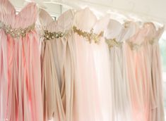 Bridesmaid dresses in different soft colors and sparkly belts. IN LOVE!