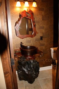 Old growth redwood burl vanity with copper sink and pump style faucet. The base is a redwood root. The mirror is a live edge redwood burl mirror
