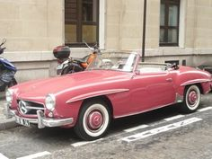 Pink vintage Mercedes parked on a Parisian street.