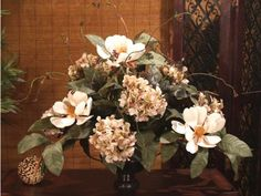 "Elegant Magnolia and Hydrangea Silk Floral Arrangement AR146-74. Gorgeous creamy yellow silk magnolias accented with warm browns are arranged with hydrangeas in a round metal vase to create the perfect centerpiece for your table. Silk Magnolia Centerpiece measures 19""H x 21""L approx."