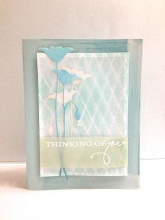 "By Pam. Drag a white ink pad over light blue cardstock card front. On this, pop up a white cardstock panel that was misted over packaging material.Die cut ""Prim Poppies"" (Memory Box) from white & light blue. Attach white one to the misted cardstock. Lay vellum over the die-cut. Layer the blue poppies on top of the vellum. Stamp sentiment in VersaMark & emboss with white powder on a colored vellum strip."