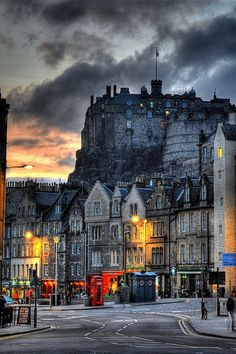 -Edinburgh Castle, Scotland       Photo by David P.   I want to go to Edinburgh really, really badly.   Plane tickets from Geneva to Edinburgh sadly appear to rather extravagant, so this is going on the back burner for the time being.   [desc. a street with many row houses with shops on the first floor, with a castle and a stormy-looking sunset-ish sky above.]