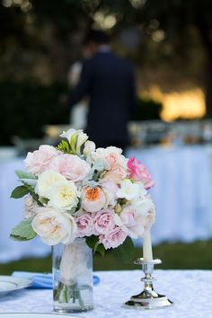 The bride rests her bouquet upright in a simple glass vase. HD Video Memories & Photography.
