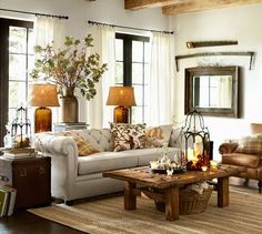 Coffee table decor n side table, pillows, glass lamps on sofa table behind sofa, basket under coffee table, black trim, white walls and curtains