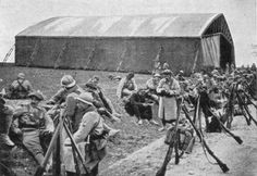 French troops rest outside a temporary aircraft hanger on their way to Verdun during the battle of 1916.