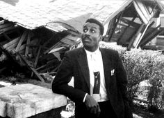 Rev. Fred L. Shuttlesworth standing in front of his home. This picture was taken after his home was bombed by the Klu Klux Klan.