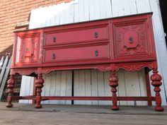 This large old buffet has been painted in a Tomato Red, distressed and glazed in java. The top has been stripped and dark stained, original pulls in Oil Rubbed Bronze with a touch of Spanish Copper. The interior has been freshened with the same super dark and shimmery Oil Rubbed Bronze.