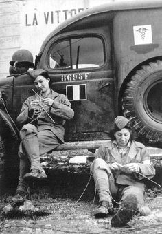 Two women of the Free French ambulance corps take time out for knitting while awaiting their next call somewhere on the Italian front in 1944.