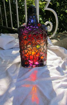 Bottle painted with glass paint, mosaiced in clear glass - beautiful idea for those big olive oil bottles Maybe for the yard
