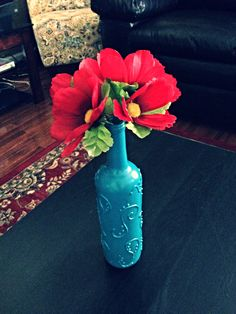 Remove label from wine bottle - use puffy paint to draw your own design - spray paint over the whole thing - add flowers