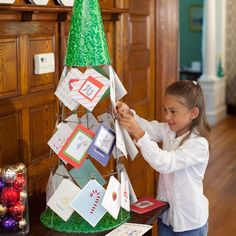 holiday card display: Here is one I have not seen before, an upcycled tomatoe cage as a christmas tree that holds the cards!  How cute!  They also suggest using tied jingle-bells as card grips!  christmas card display, card holder, diy craft from: http://www.momsshoppingengine.com/community/315/#
