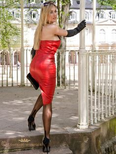 Tight Red Leather Dress With Visible Garter Bumps Black Leather Gloves Sheer Black Back Seam Stockings and Black Stiletto High Heels