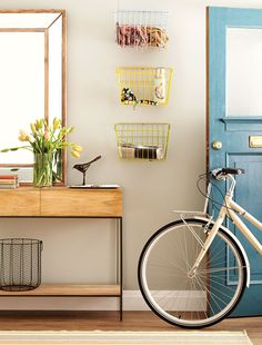 Looking for a space-saving storage solution for your entryway? Why not attach some inexpensive bicycle baskets to your wall.
