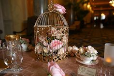 Vintage centerpiece for a sweetheart table consisting of a gold birdcage filled with roses in various shades of pink and baby's breath. Teacups filled with matching flowers completed the look. (Designed by Janelle Gerestein of Creative Weddings Floral Designs)