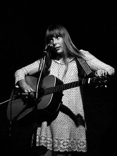 Joni Mitchell tunes her guitar on stage (1968)