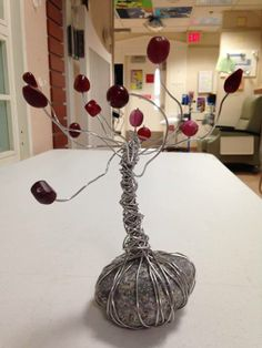 using a beach pebble  and used soft armature wire and beads to create this amazing sculpture of a tree.