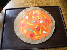 Pizza for the letter P from brown paper bags lightly stuffed with newspaper and cardstock toppings.