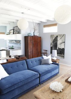 This stunning living room design by Emily Henderson gets a jolt of color from a pretty blue sofa. Store your things in a wood armoire and on top of a sofa table.