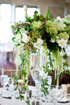 "2 Tall arrangements of cream hydrangeas, blue privet berries, ivory roses, grey dusty miller, scabiosa pods, purple-grey succulents, green hanging amaranthus, and dripping clematis vine on top of a 32"" cylinder vase sitting atop an ivory stone pedestal will frame the ceremony site."