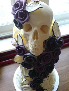 a beautiful wedding cake with black and purple roses and a white chocolate skull. this is so cool!!!