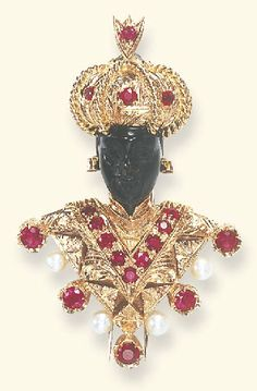 A DIAMOND, RUBY AND HARDSTONE BLACKAMOOR BROOCH, BY NARDI  The carved hardstone blackamoor wearing an etched rose gold turban enhanced by circular-cut ruby accents and an oval-cut garnet surmount, with circular-cut ruby ear pendants and a tunic of similar design, accented by cultured pearl and circular-cut ruby trim, mounted in 18k rose gold