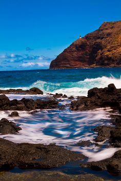 Makapuu Lighthouse - Waves rolling in and crashing against the rocks with Makapuu Lighthouse in the distance.