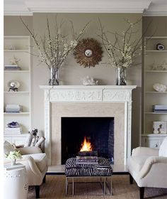 Benjamin Dhong - living room - fireplace carved trim, seating, footstool, open shelving
