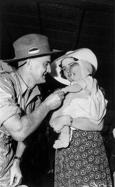 Soldier dad greeting his wife and baby on arrival home on leave from Darwin, Brisbane, November 1941