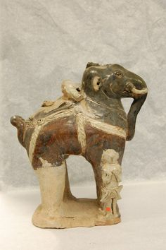 Figure. Stoneware brown and cream glazed figure of an elephant. With the remains of driver and warriors, and details in white. Sawankhalokm,14th -16th Century