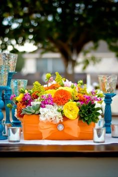 The low centerpieces will be varied sizes of orange fabric-wrapped boxes with small brooch accents filled with pink hydrangeas, fuchsia phalaenopsis orchids, orange tulips, red pincushions, fuchsia garden roses, red hypericum berries, and blue succulents surrounded by mercury glass votives and a trio of blue pedestals topped with mercury glass candles.