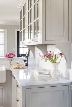 inset white cabinets, corbels (brackets) under upper glass cabinets on backsplash.